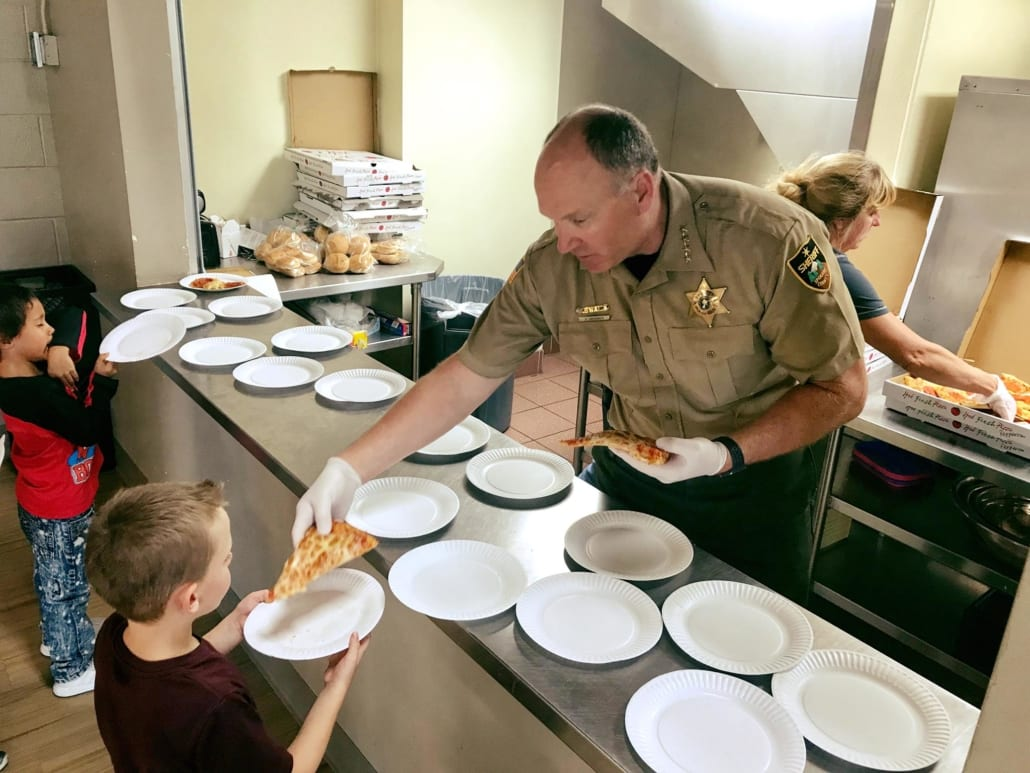 Sheriff Ozzie handing out Pizza to kids