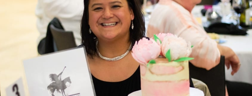Woman holding a cake she won at the dinner auction